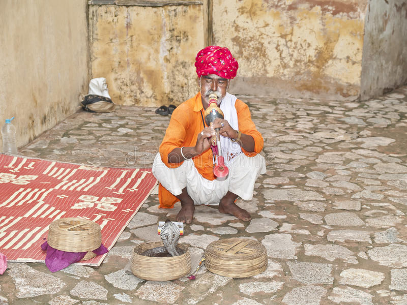 Snake charmer, Jaipur, India. Snake charmer receiving tips on August 10, 2012 in Jaipur, India.Today, only about one million snake charmers remain in India royalty free stock photography