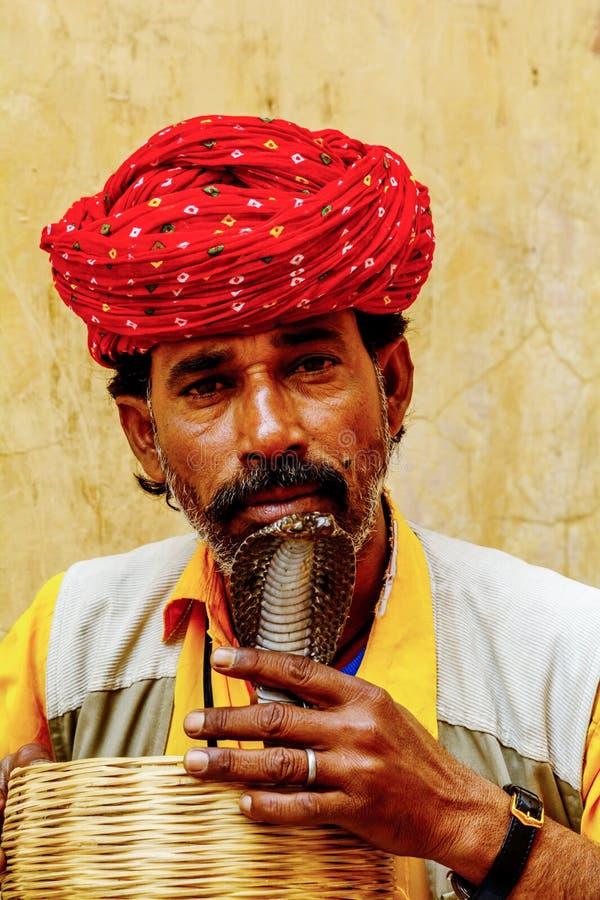 Snake charmer kissing snake in Jaipur, India. Jaupur, India- March 12, 2015: Snake charmer kissing snake in India stock photography