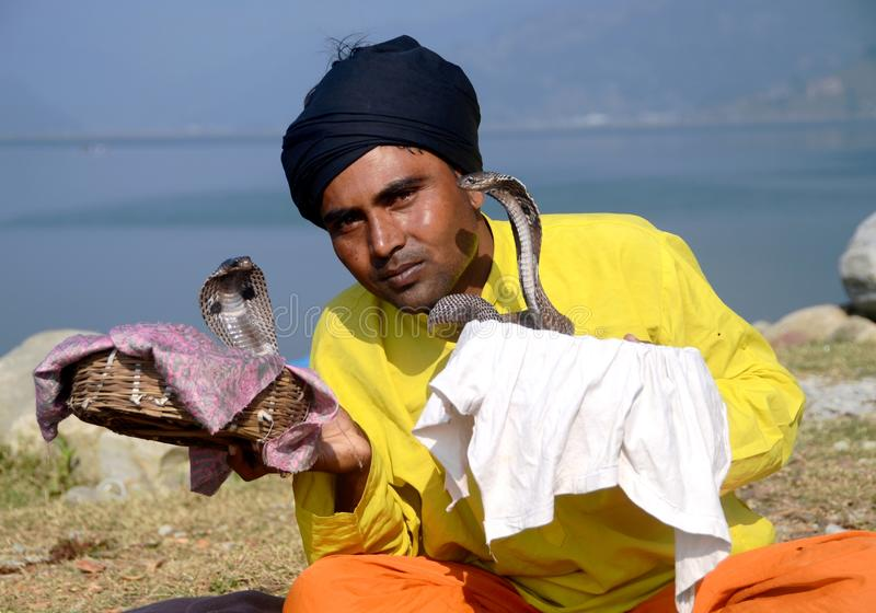 Snake charmer in Nepal. Snake charmer performs on the shores of Phewa lake in Pokhara, Nepal royalty free stock photos