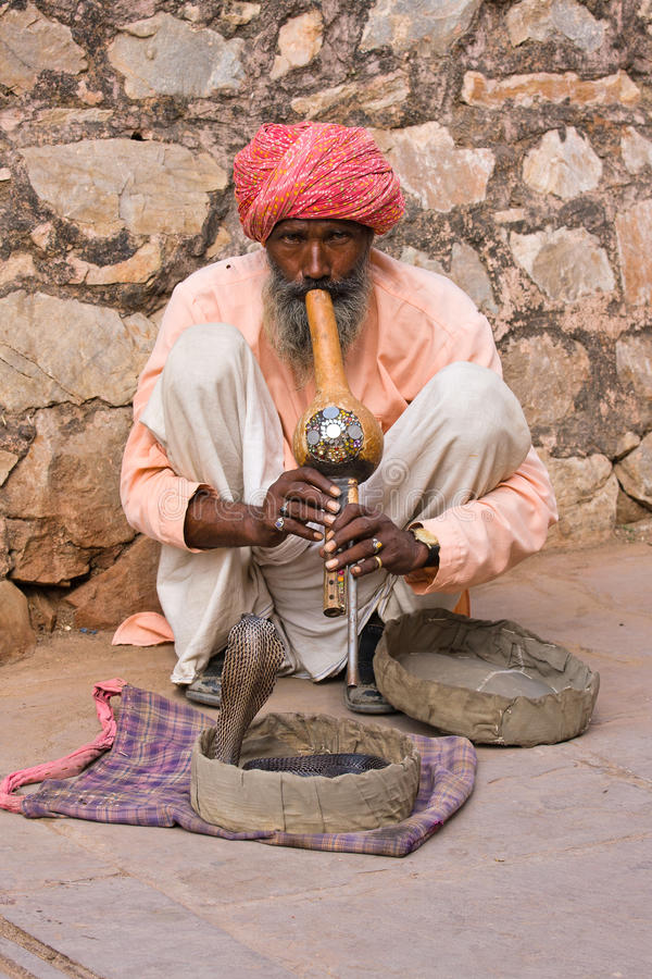 Snake charmer is playing the flute for the cobra in Jaipur, India. JAIPUR, INDIA - NOVEMBER 10, 2012: An unidentified snake charmer is playing the flute for the royalty free stock images