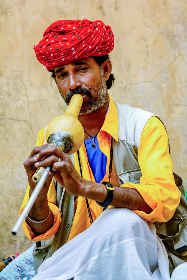 A snake charmer is playing the flute for the snake. Jaipur, India- March 12, 2015:: A snake charmer is playing the flute for the cobra sitting b the wall in the royalty free stock photo