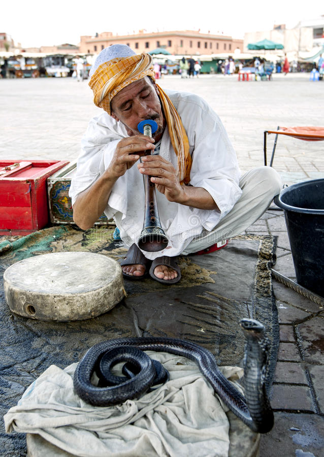 A snake charmer plays his flute towards a cobra in Djemaa el-Fna, the main square in the Marrakesh medina in Morocco. Marrakesh, founded in 1062 by Abu Bakr stock photography
