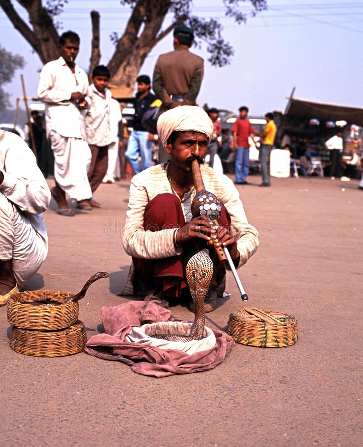 Snake charmer by the Red Fort, Delhi. Snake charmer tempting cobra snakes out of their wicker baskets outside the Red Fort, Delhi, Delhi Union Territory, India stock image
