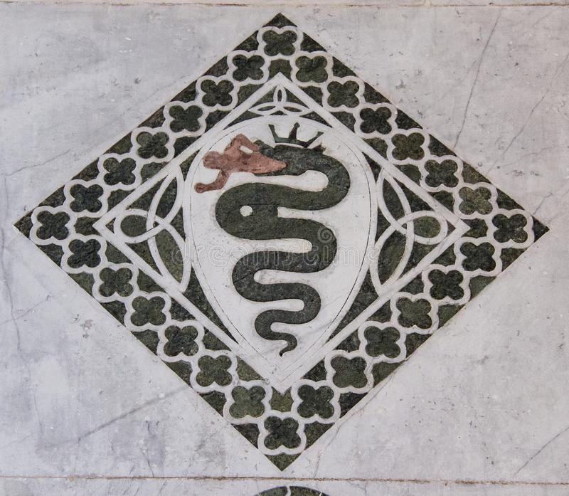 Snake eating a man in a decorative quad on the Chiesa dei Santi Giovanni e Reparata. Snake eating a man in a decorative quad stock photo