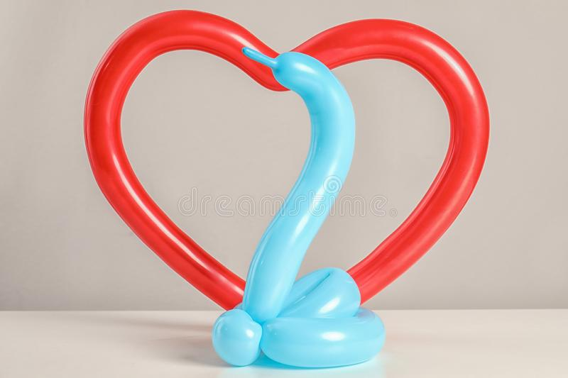 Snake and heart figures made of modelling balloons on table stock photo