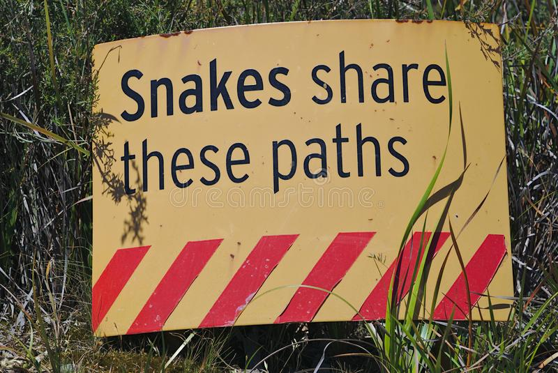 Snakes share these paths warning sign. In yellow color with red diagonal stripes stock image