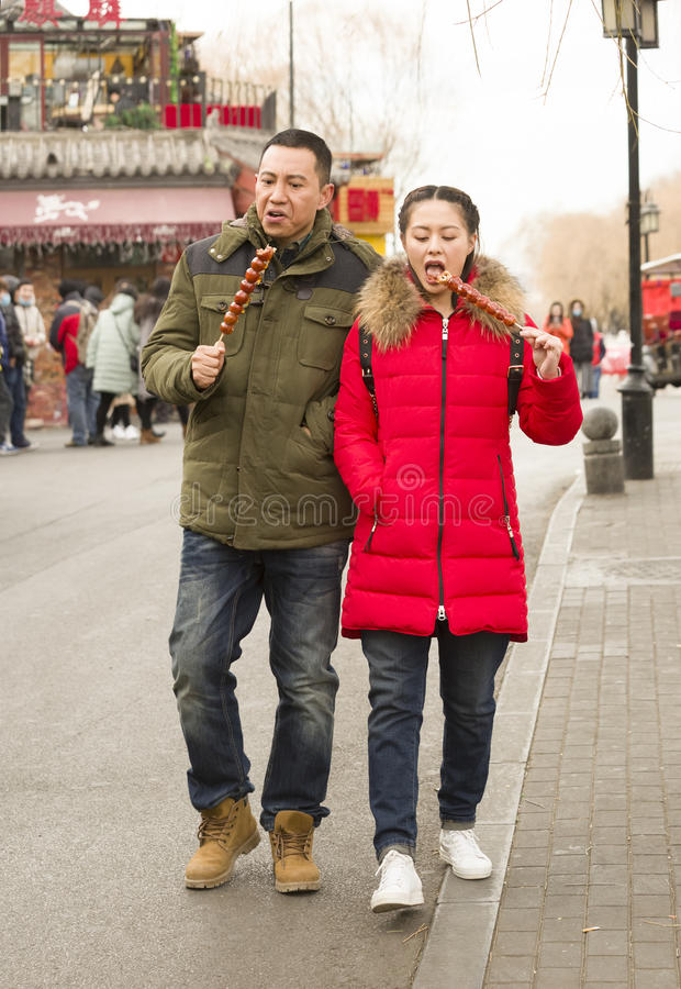 Snap portrait at a TV play production site. A couple in coat are being acted as the roles in the TV play is snapped when they are walking and eating sticked stock photography