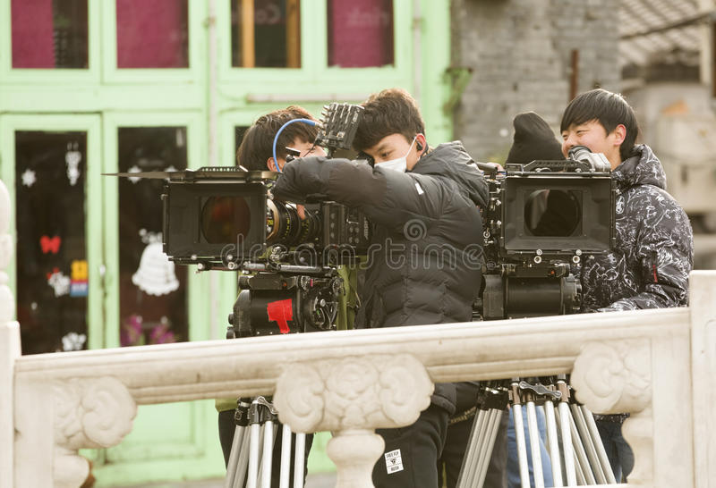 Snap portrait at a TV play production site. Three cameramen in coat are debugging the vidicons before the TV play is producing in a traveling area in Beijing royalty free stock photography