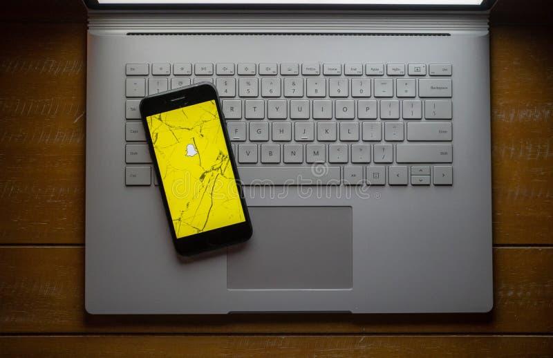 Snapchat app на сломленном сотовом телефоне сидя на компьтер-книжке стоковое изображение