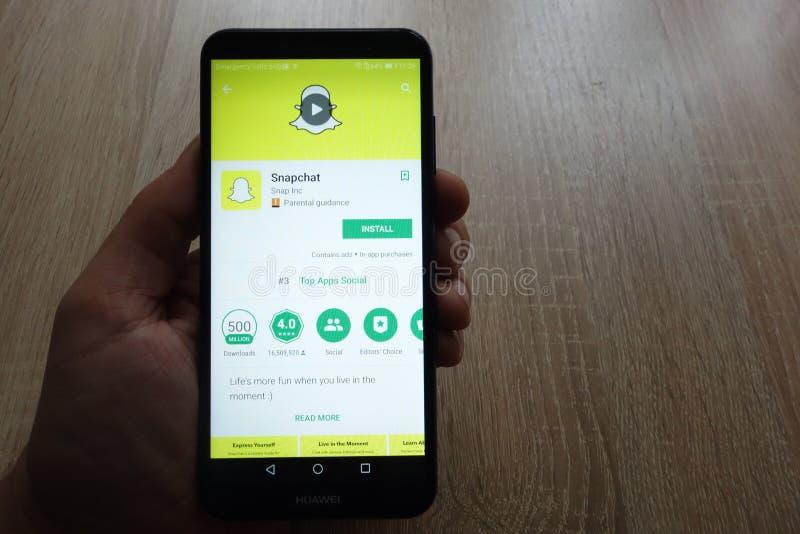 Snapchat app on Google Play Store website displayed on Huawei smartphone in man`s hand. KONSKIE, POLAND - JUNE 17, 2018: Snapchat app on Google Play Store stock photo