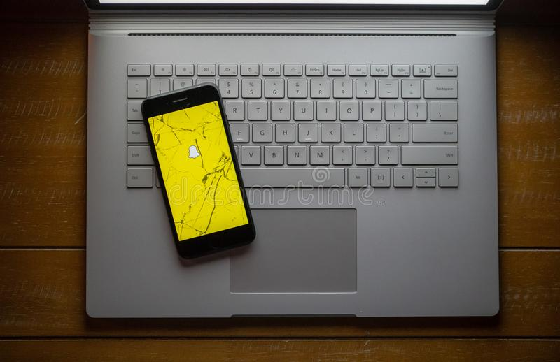 Snapchat app op een gebroken zitting van de celtelefoon op laptop stock afbeelding
