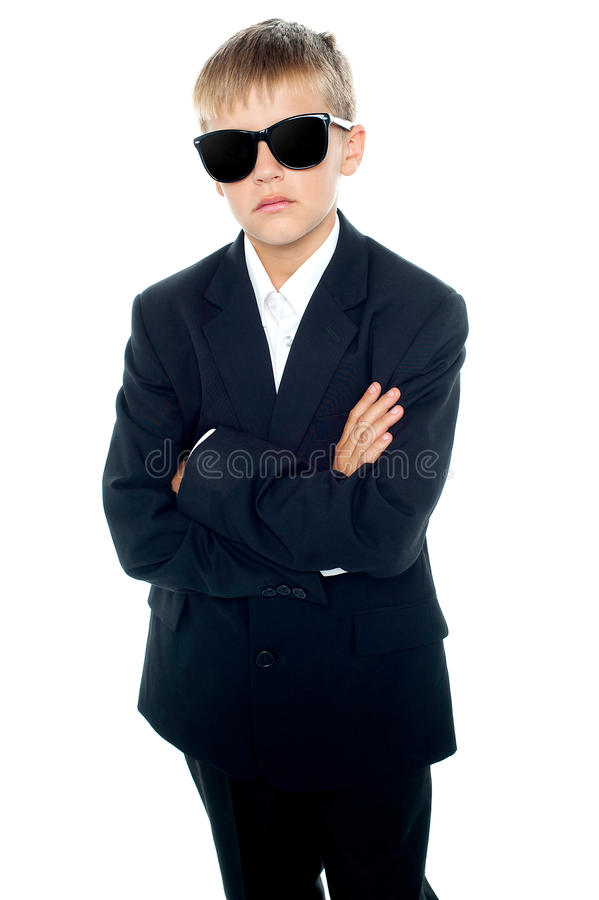 Snapshot of young kid wearing suit and sunglasses. Posing with confidence royalty free stock photos