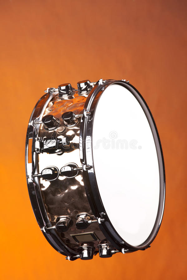 Snare Drum Copper Isolated. A copper snare drum isolated against a yellow or gold background in the vertical format royalty free stock photography