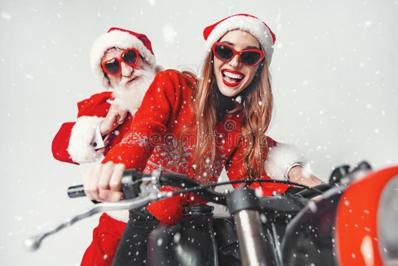 Snata Klaus mit neues Jahr-Mädchen auf dem Fahrrad stockbild