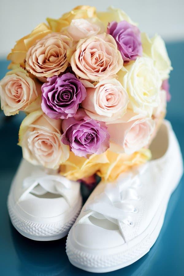 Sneackers bianchi del ` s della sposa e bello mazzo nuziale fotografia stock