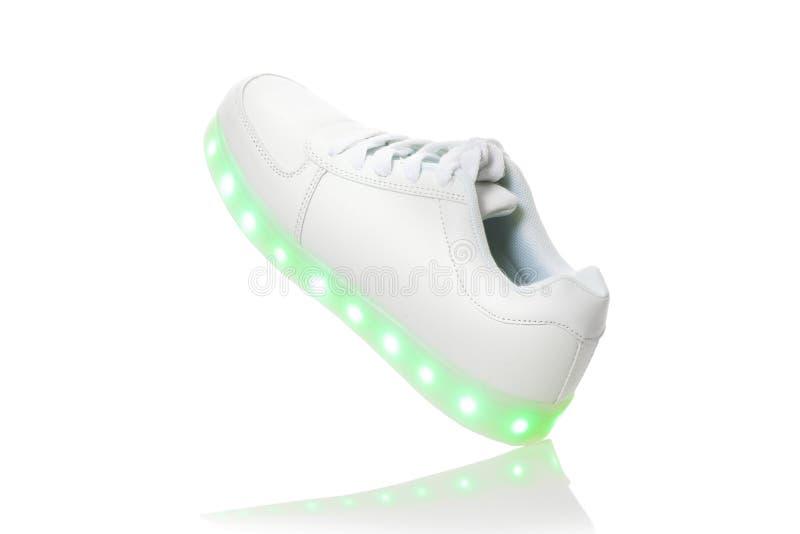 Sneackers brancos com a sola clara conduzida foto de stock