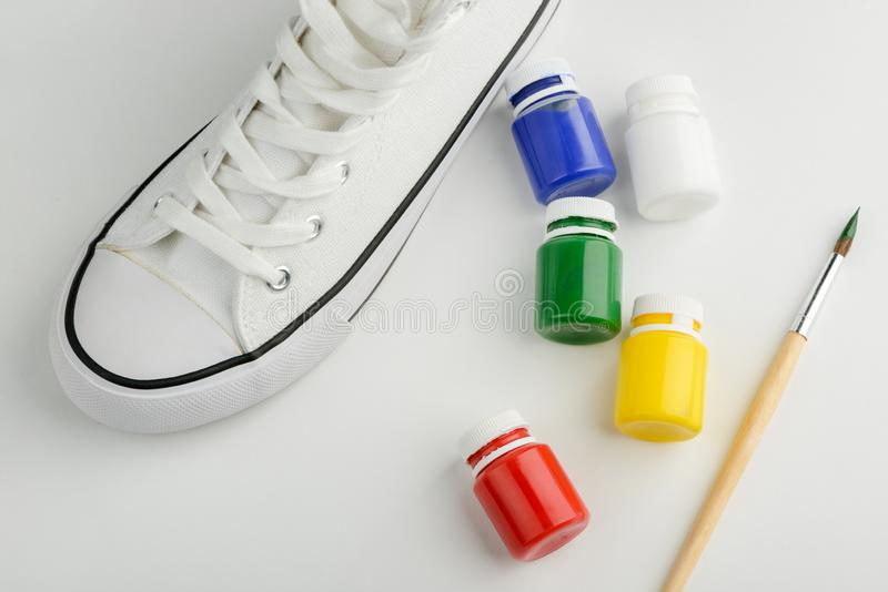 Sneaker, paint and brush. Blank canvas sneaker, paint and brush on white background. Custom design, creative project for DIY blog stock images