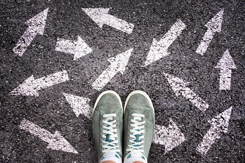 Sneaker shoes and arrows pointing in different directions on asphalt, choice concept royalty free stock photo