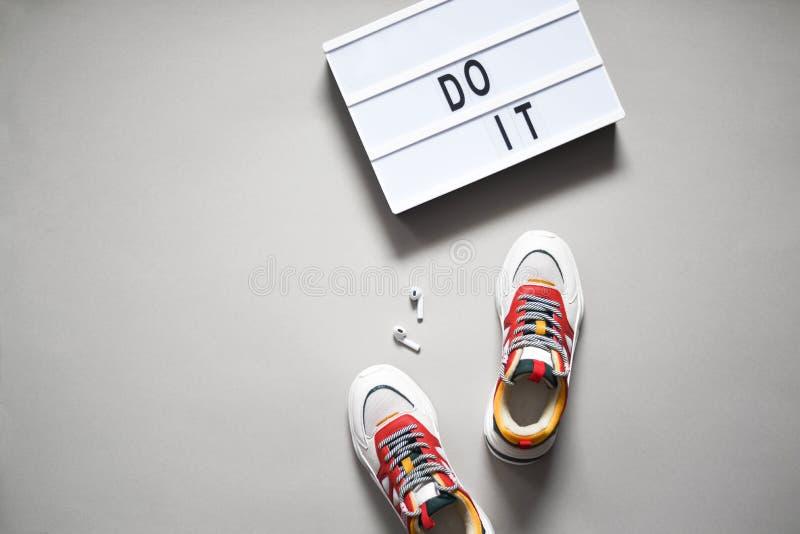 Sneakers, audífonos y un letrero diciendo que lo hagan imagen de archivo libre de regalías