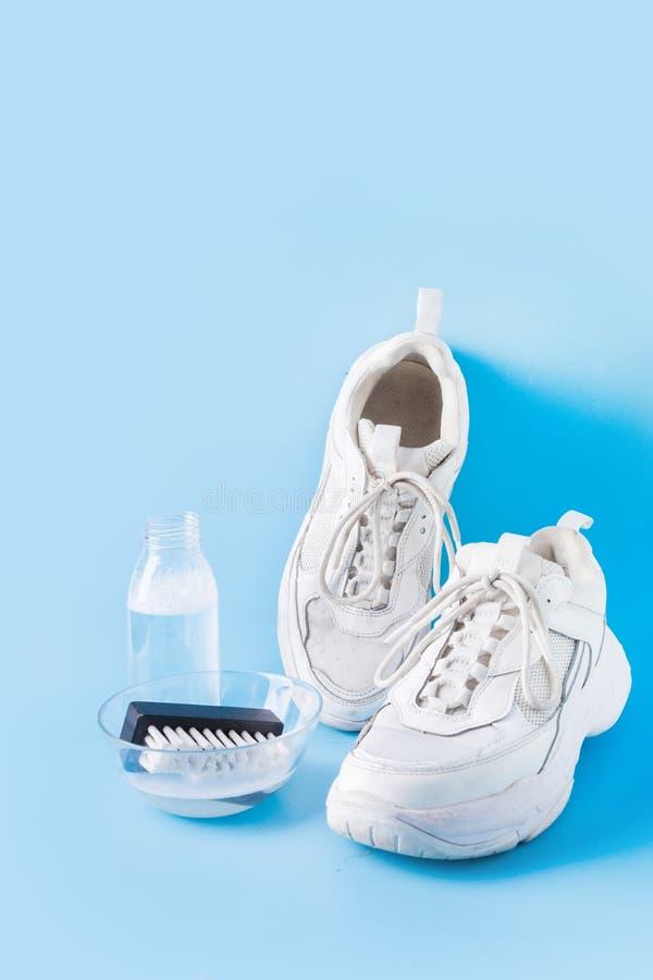 Sneakers blancos sucios con una herramienta especial para limpiarlos en azul imagen de archivo