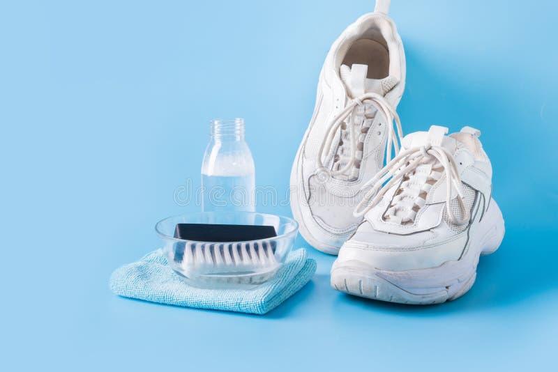 Sneakers blancos sucios con una herramienta especial para limpiarlos en azul fotografía de archivo