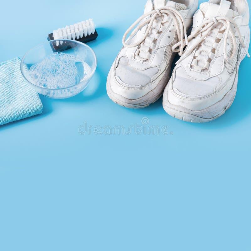 Sneakers blancos sucios con una herramienta especial para limpiarlos en azul imágenes de archivo libres de regalías
