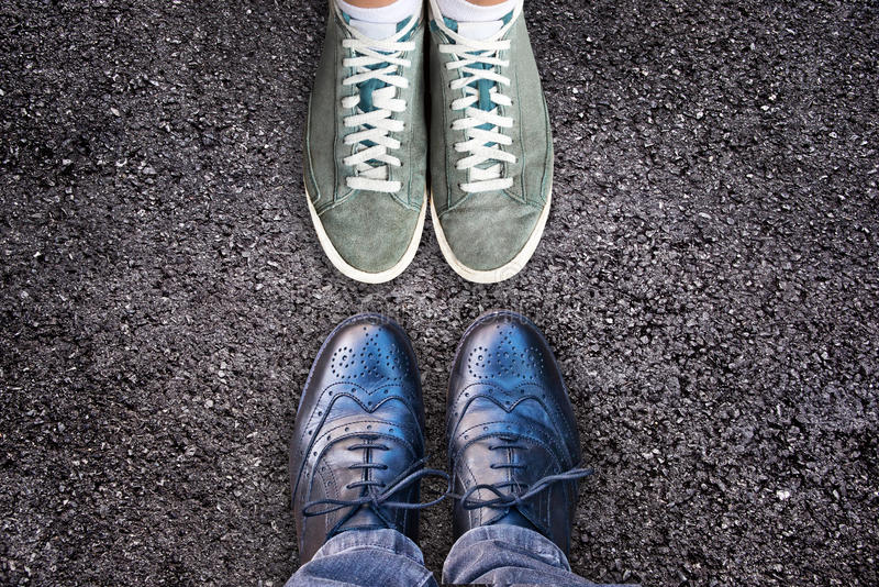 Sneakers and business shoes face to face on asphalt, work life balance concept. Sneakers and business shoes face to face on asphalt - work life balance concept royalty free stock image