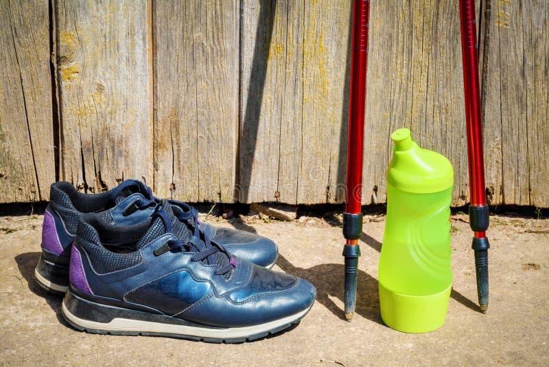 Sneakers, butelka wodni i Północni chodzący słupy blisko drewnianej ściany obraz royalty free
