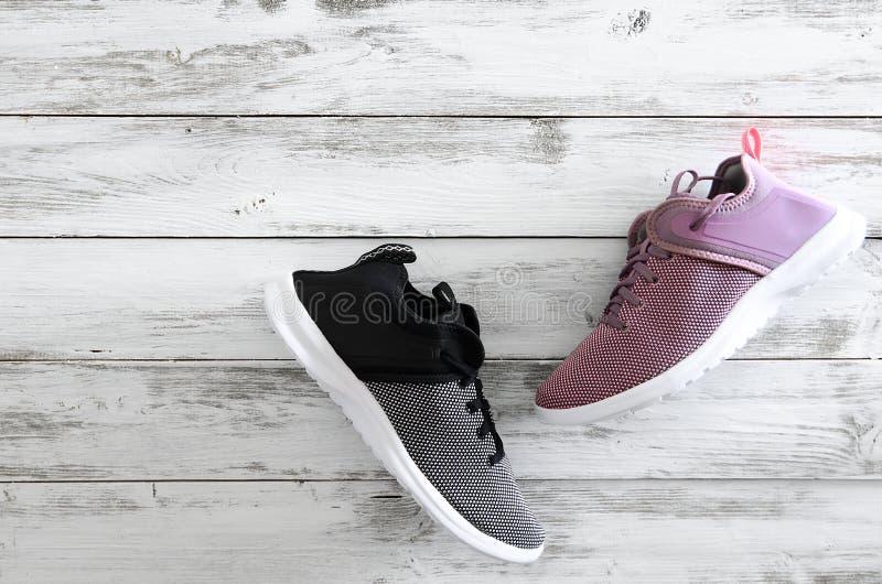 Sneakers fiołek, czarny i biały na drewnianym tle z co fotografia royalty free