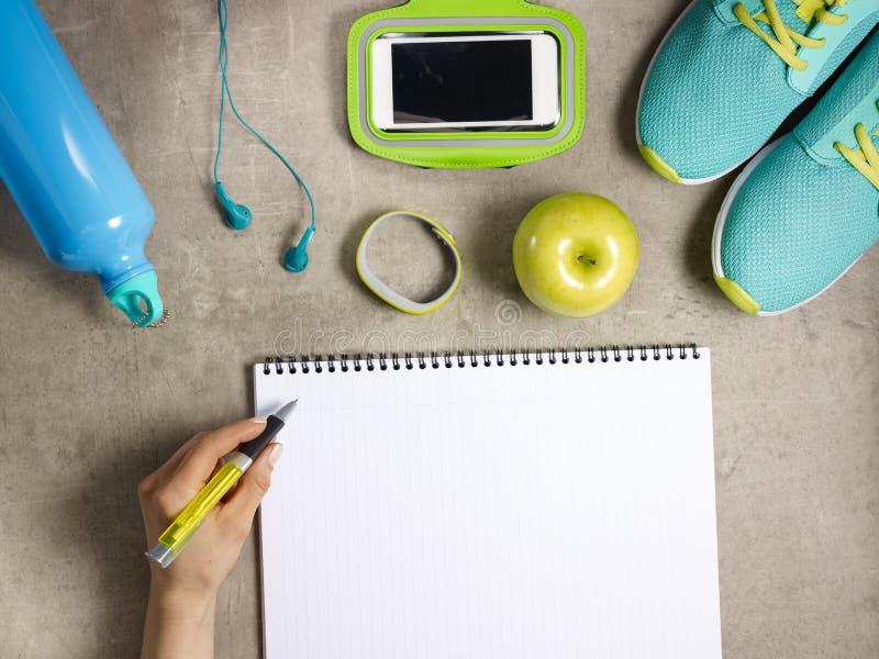 Sneakers, fitness tracker en vrouwelijk handschrift in laptop royalty-vrije stock afbeelding