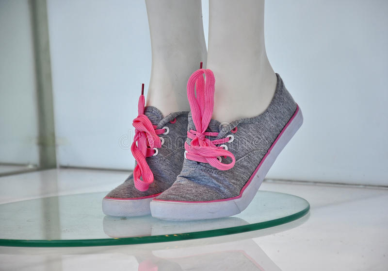 Sneakers for girls. On mannequin in store window stock image