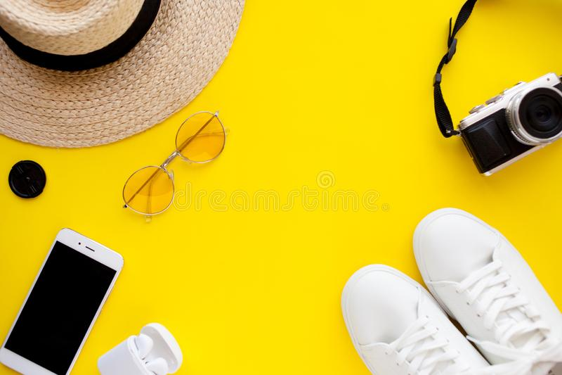Sneakers, hat, sunglasses, wireless headphones, smartphone and photo camera are lying on a bright yellow background. royalty free stock photography