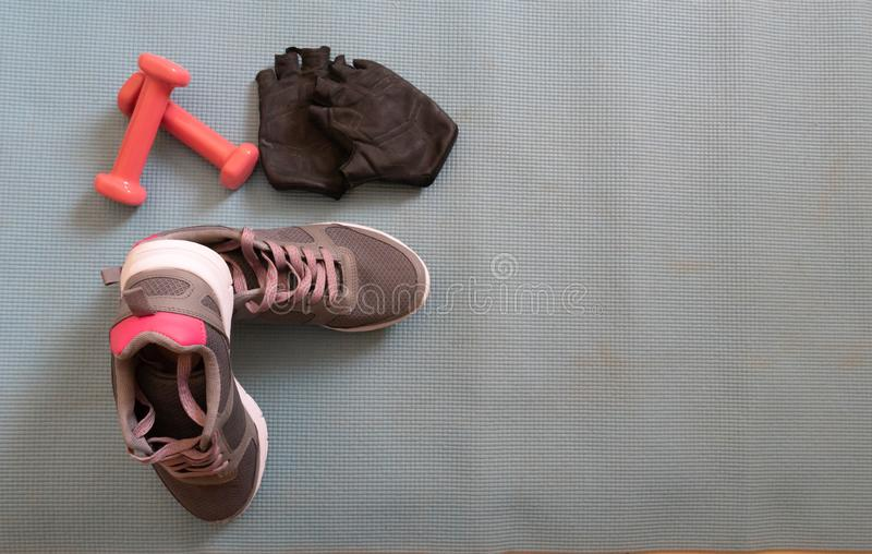 Sneakers ready to training at home, making exercise in a fitness class with muscular equipment. Jumping rope, pink dumbbells and royalty free stock images