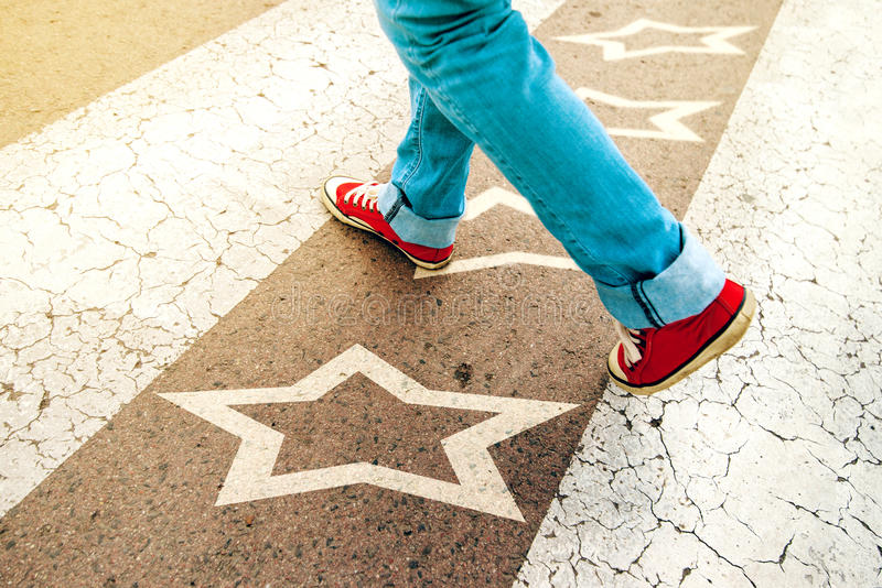 Sneakers on the road with star shape imprint stock photo