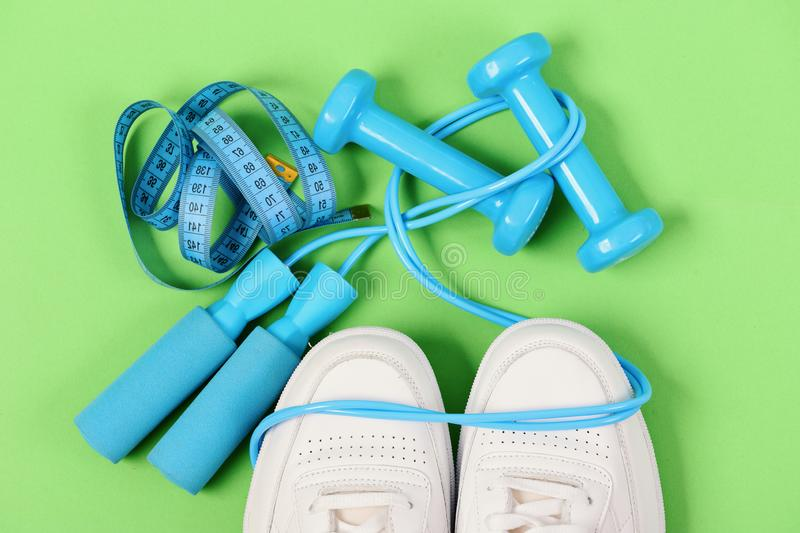 Sneakers with skipping rope and tape on green background. Jogging and healthy lifestyle concept. Dumbbells in cyan blue color on white trainers, top view stock photo