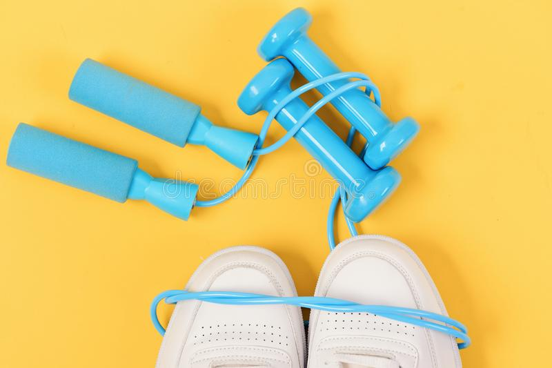 Sneakers with skipping rope on yellow background. Dumbbells in cyan blue color on white trainers, top view. Jogging, sports and healthy lifestyle concept stock images