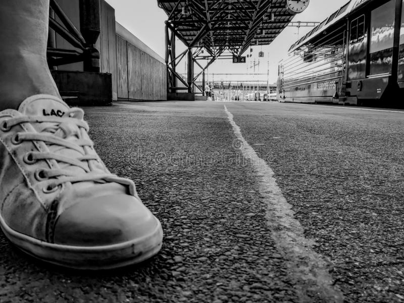 Sneakers on train station in black and white stock image