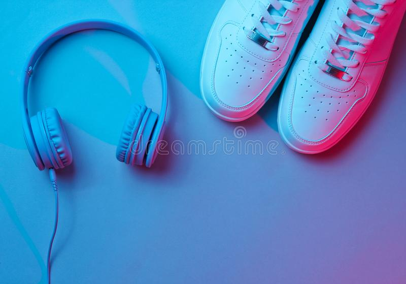 Sneakers with wireless headphones. Retro wave, neon light, ultraviolet. Top view, minimalism stock images