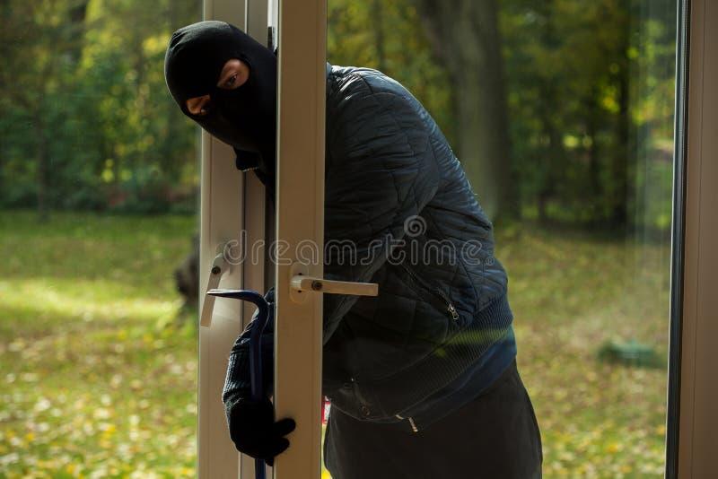 Sneaking through window. A masked burglar sneaking through the window royalty free stock photography