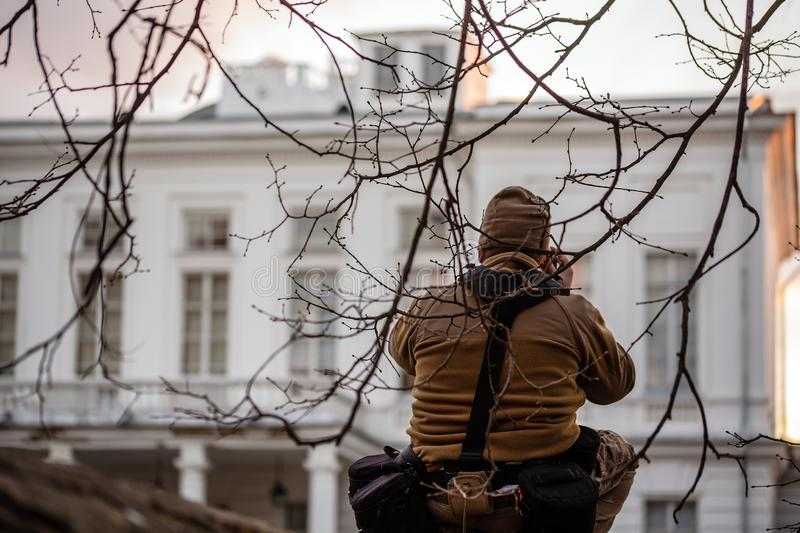 Sneaky professional photographer shooting private white building facade from fence under tiny brcnches. Pro gear weared with belt pouches and fleece coat royalty free stock images