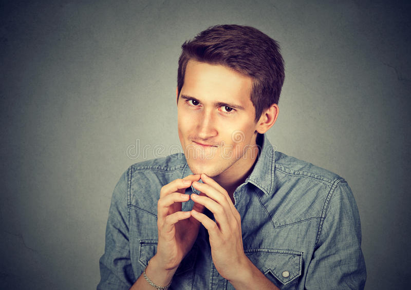 Sneaky scheming young man plotting something. Isolated on gray wall background. Negative human emotion facial expression feeling attitude stock image