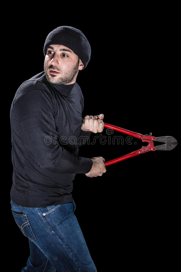 Sneaky Thief. A burglar wearing black clothes holding huge wire cutters over black background stock images