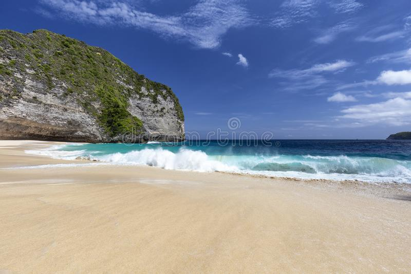 Sneaky Tropical Waves. Waves crashing on the shore of Kelingking beach on Nusa Penida in Indonesia royalty free stock photos