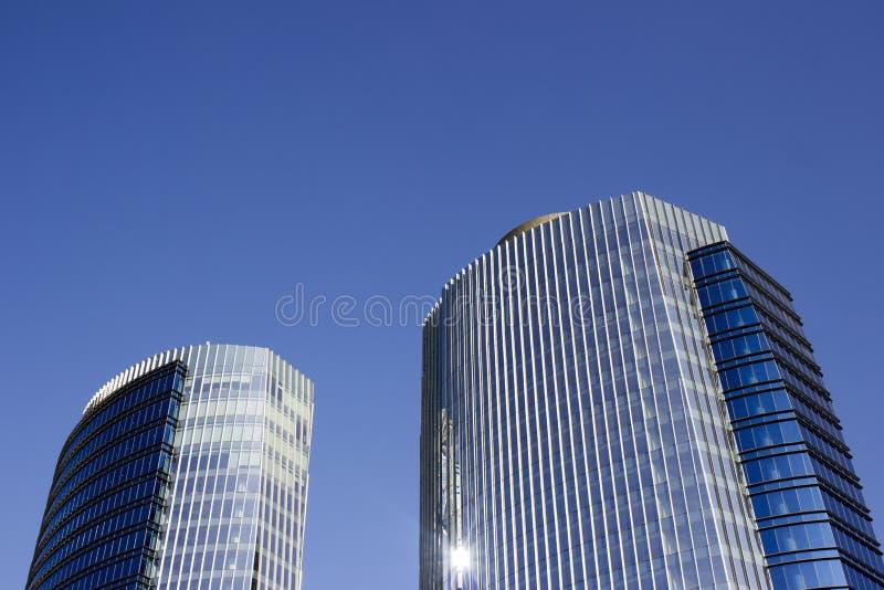Sned bollskottet av ett par av kopplar samman företags blåa kontorshöghus med en randig design royaltyfria bilder