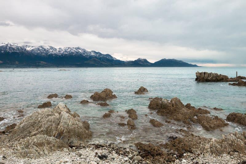 Sneeuw behandelde bergen op oceaankust royalty-vrije stock foto's