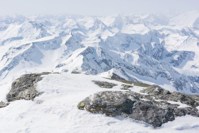 Sneeuw behandelde rots met een bergmening in de rug royalty-vrije stock fotografie