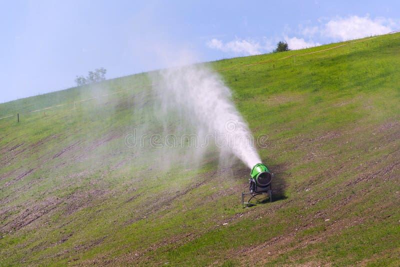 Sneeuw die machines maken die aan watergras worden gebruikt op helling, zonnige de zomerdag, Wagrain-skitoevlucht stock afbeelding