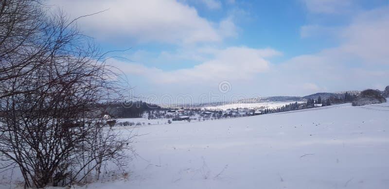 Sneeuw en blauwe hemel met wolken en stok royalty-vrije stock afbeelding