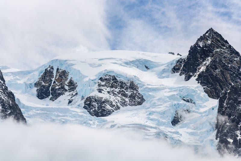 Sneeuw en gletsjerijs behandelde rotsachtige bergpiek, met mist hieronder en lichte witte wolken in een blauwe hemel hierboven, D royalty-vrije stock afbeelding
