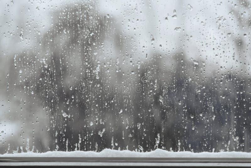 Sneeuw en regendalingen op een venster, slecht weerachtergrond met cop stock afbeeldingen